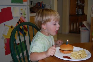 Caden blowing out his cheeseburger candle